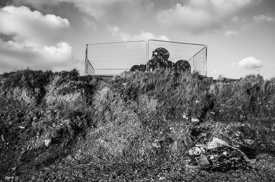 Grass topped bank with cage and rubbish pile on beach. Shoreham Sussex UK. Monochrome Landscape. © P. Maton 2015 eyeteeth.net