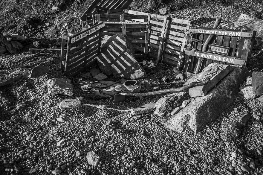 Beachcomber's den mad from pallets on shingle beach with makeshift tool and collected items and signs saying - Start Where You Are, Use What You Have, Do What You Can. Shoreham Beach Sussex UK. Monochrome Landscape. © P. Maton 2015 eyeteeth.net