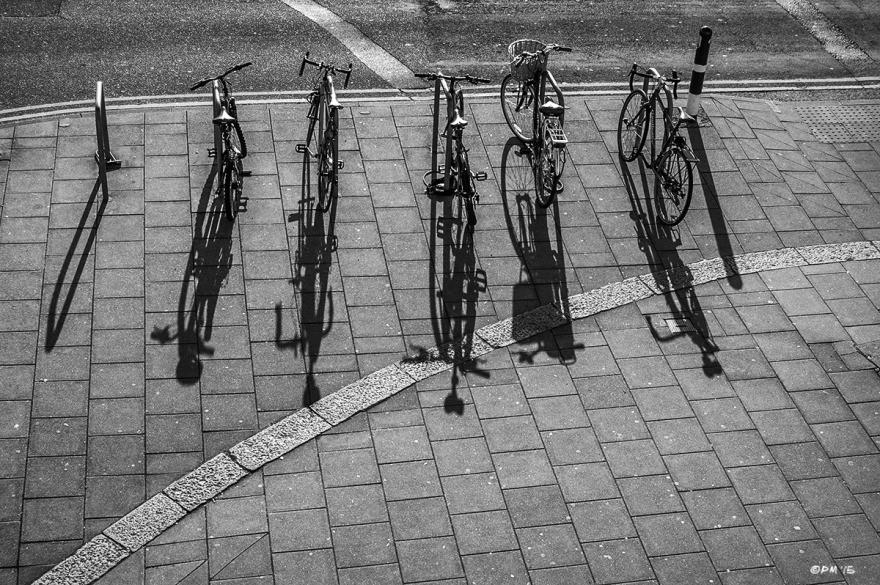 Line of parked bicycles on edge of pavement by road casting shadows. Marine Parade Brighton UK. Monochrome Portrait. © P. Maton 2015 eyeteeth.net