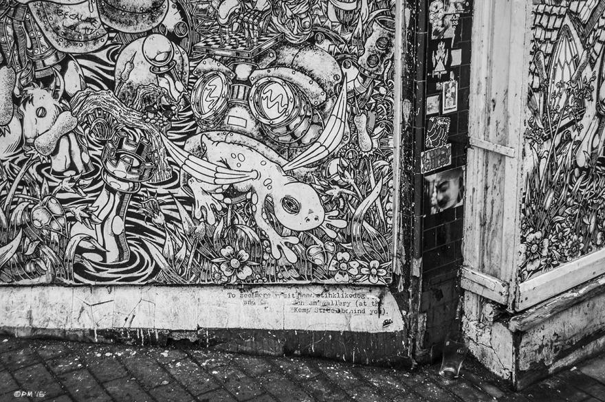 Complex drawing by Etienne on shutters at street corner with pint glass. Street Art. Trafalgar Street, Brighton UK. P. Maton 2015 eyeteeth.net