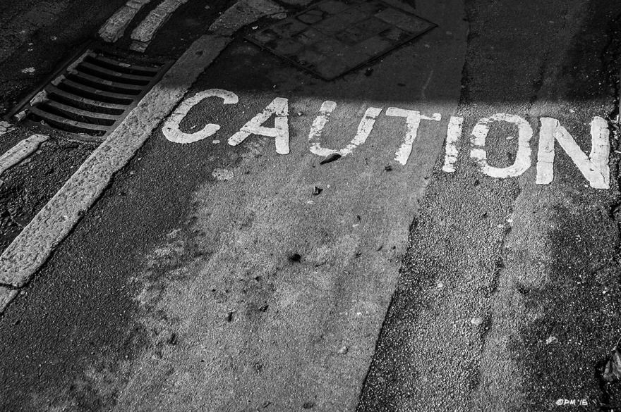 Caution notice written on pavement / sidewalk next to raod with drain grille and shadow. Viaduct Road, Brighton UK. Monochrome Landscape. © P. Maton 2015 eyeteeth.net