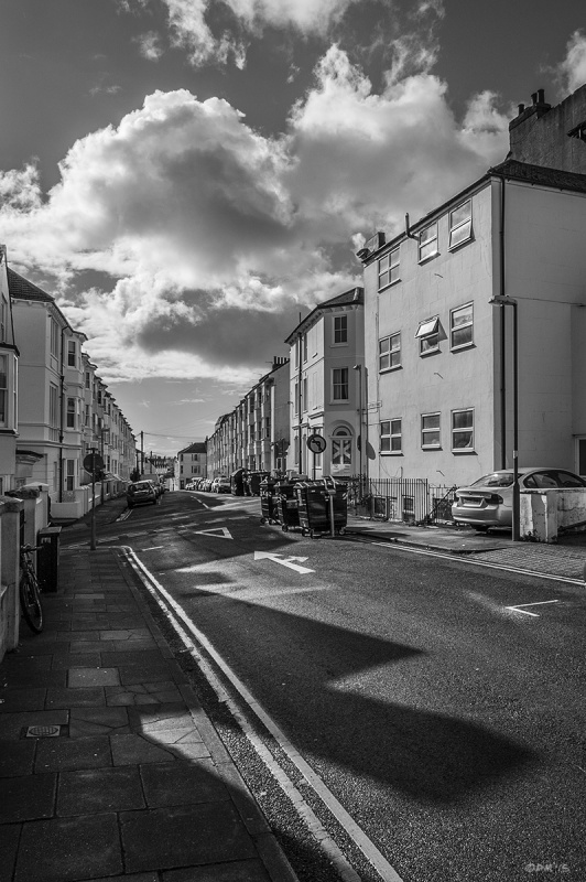 View along Georgian terraced town street  with looming shadows and billowing clouds. Clifton Street with junction to Buckingham Street, Brighton UK.  Monochrome Portrait. © P. Maton 2015 eyeteeth.net