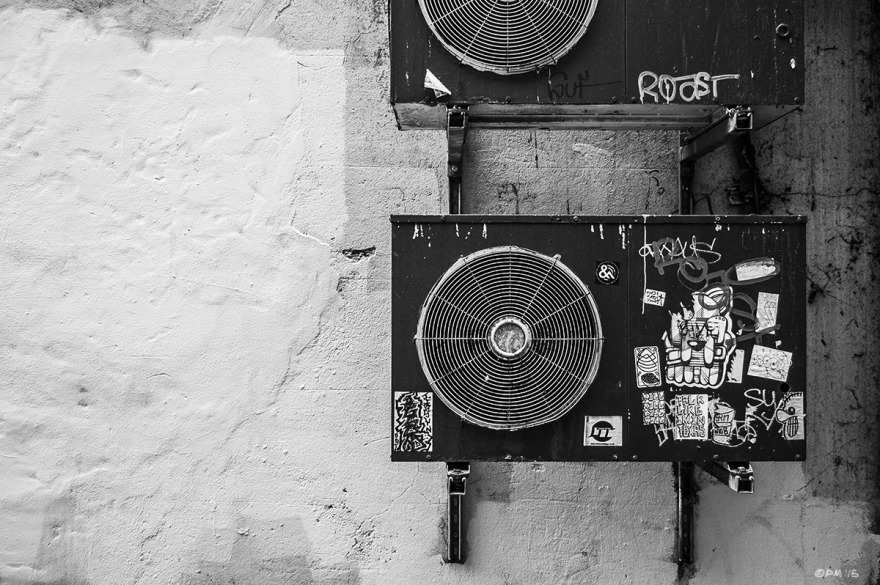 Extractor fans on uneven wall with stickers.  Zion Gardens, Brighton UK. Monochrome Landscape. © P. Maton 2015 eyeteeth.net