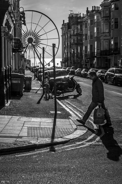 Man with shopping bag crossing road with street leading to sea and Brighton Eye big wheel in background. Madeira Place, Kemptown Brighton UK. Monochrome Portrait. © P. Maton 2015 eyeteeth.net