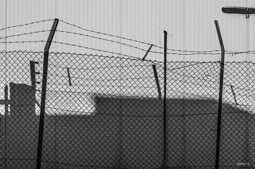 Chicken wire and barbed wire fence casting shadow on metal warehouse wall. Basin Road South, Hove  UK. Monochrome Landscape. © P. Maton 2015 eyeteeth.net