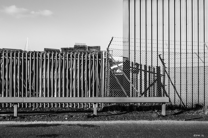 Metal fences and warehouse wall next to road, abstract textures.  Basin Road South Shoreham Harbour, Hove UK. Monochrome Landscape. © P. Maton 2015 eyeteeth.net