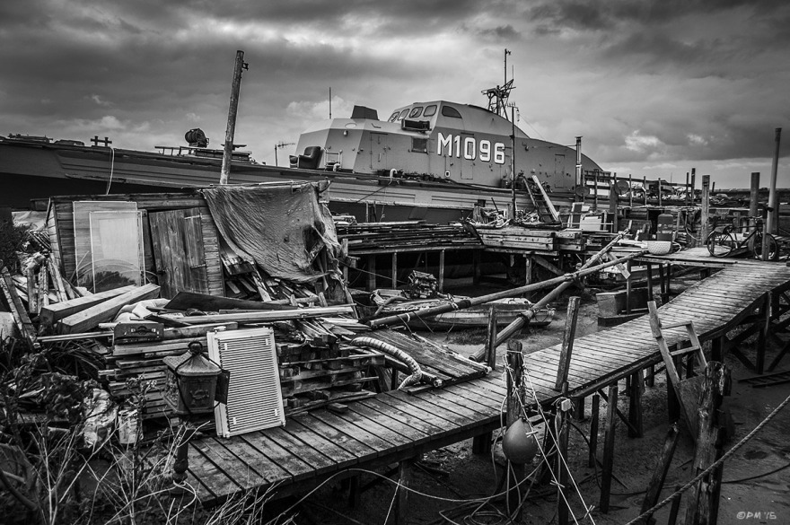 Minesweeper 'Fische' M1096 moored  next to Jetty with  piles of wood and clutter.  River Adur Shoreham Harbour UK. Monochrome Landscape. © P. Maton 2015 eyeteeth.net