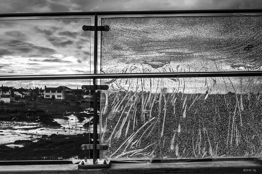 Shattered glass panel in footbridge with view of River Adur, mud flats, houses and dramatic clouds. Shoreham Harbour UK. Monochrome Landscape. © P. Maton 2015 eyeteeth.net