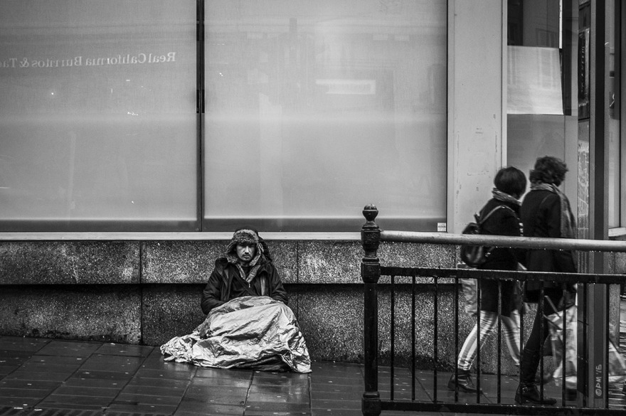 Homeless mand sitting outside bank with silver blanket in rain as couple walk passed. West Street Brighton UK. Monochrome Landscape. © P. Maton 2015 eyeteeth.net