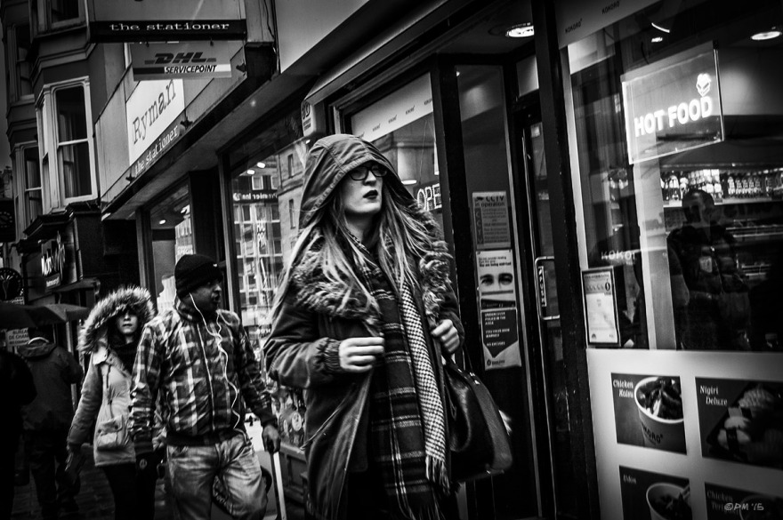 Woman in hooded coat walking through rain in front of  Kokoro Sushi and Bento restaurant. North Street Brighton UK. Monochrome Landscape. © P. Maton 2015 eyeteeth.net