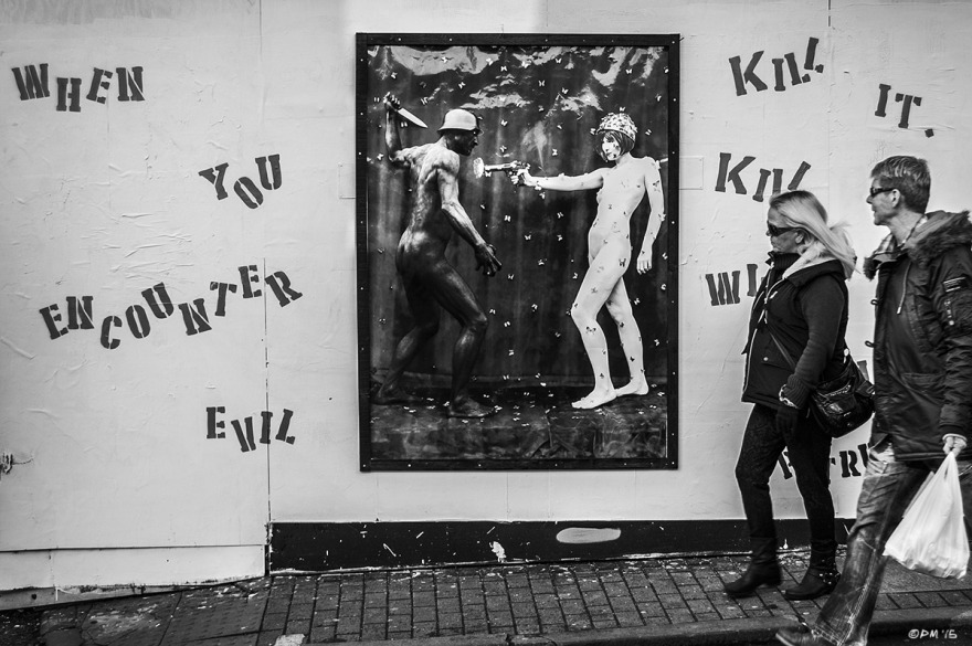 'Killing with Love' photograph installation by Petrusco on building site hoarding with couple walking passed. Trafalgar Street, Brighton UK.  P. Maton 2015 eyeteeth.net