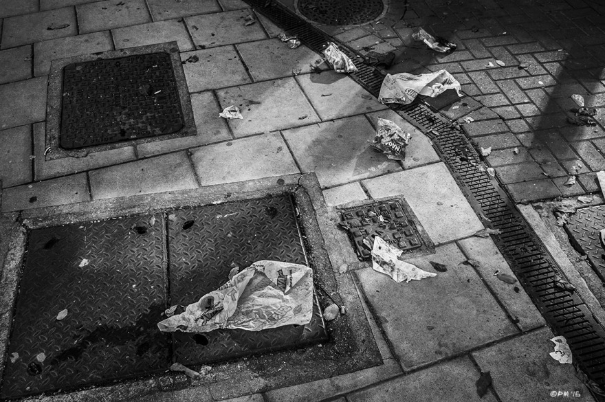 Drain covers and service wells in pavement with litter / trash and reflected light. Edward Street, Brighton UK. Monochrome Landscape. © P. Maton 2015 eyeteeth.net