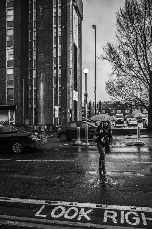 Woman with umbrella crossing road in rain with New Vantage Point tower block, traffic and 'Look Right' road marking. New England Street, Brighton UK. Monochrome Portrait. © P. Maton 2015 eyeteeth.net