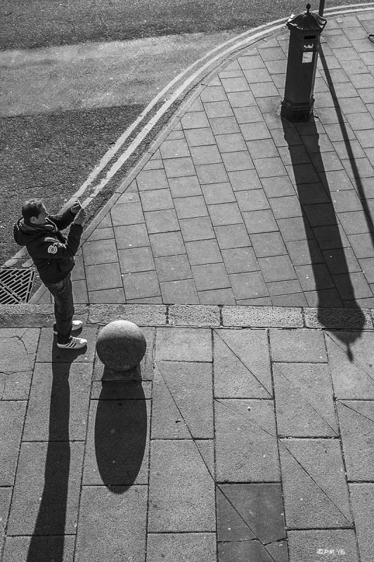 Man taking photo with smart phone seen from above . Paving slabs and post box casting long shadows. Marine Parade Brighton UK. Monochrome Portrait. © P. Maton 2015 eyeteeth.net