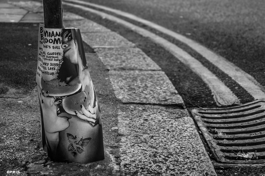 Curb stones , yellow lines and drain cover with club poster of two girls, one licking sliced water melon covering the others breasts. Kingswood Street, Brighton UK. Monochrome Landscape. © P. Maton 2015 eyeteeth.net