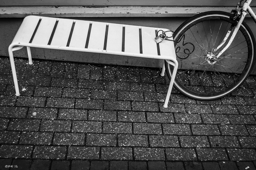 White metal bench with bicycle wheel and lock on pavement. Trafalgar Street Brighton UK. Monochrome Landscape. © P. Maton 2015 eyeteeth.net