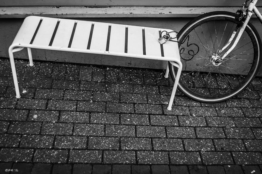 White metal bench with bicycle wheel and lock on pavement. Trafalgar Street Brighton UK. Monochrome Landscape. © P. Maton 2015 eyeteeth.net