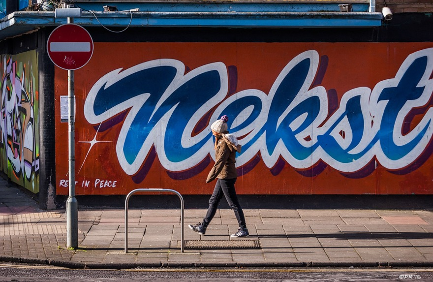 Girl in bobble hat waling on pavement in front of graffiti saying 'Nekst' by MSK. Ditchling Road, Brighton UK. Colour Landscape. © P. Maton 2015 eyeteeth.net