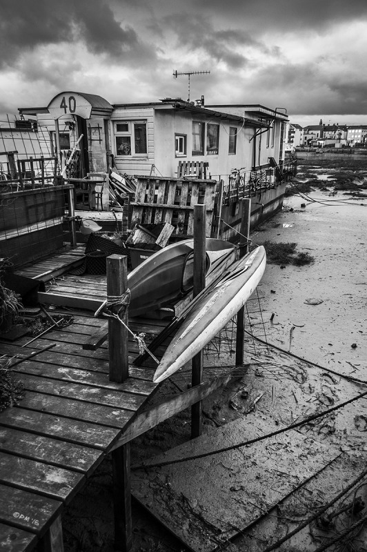 Jetty leading to houseboat with canoes over mud flats with cloudy sky.  River Adur Shoreham Harbour UK. Monochrome Portrait. © P. Maton 2015 eyeteeth.net