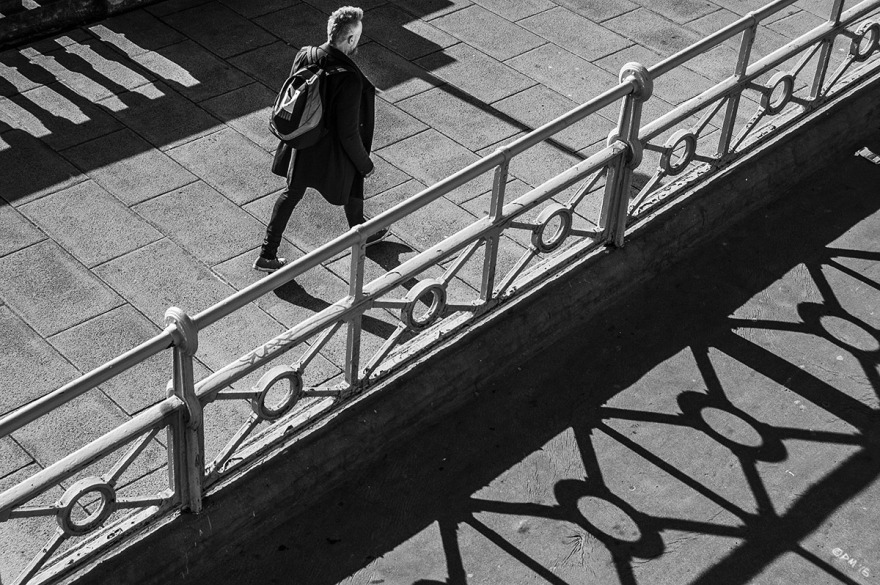 Man walking by railings casting long shadows seen from above and behind. Marine Parade Brighton UK. Monochrome Landscape. © P. Maton 2015 eyeteeth.net