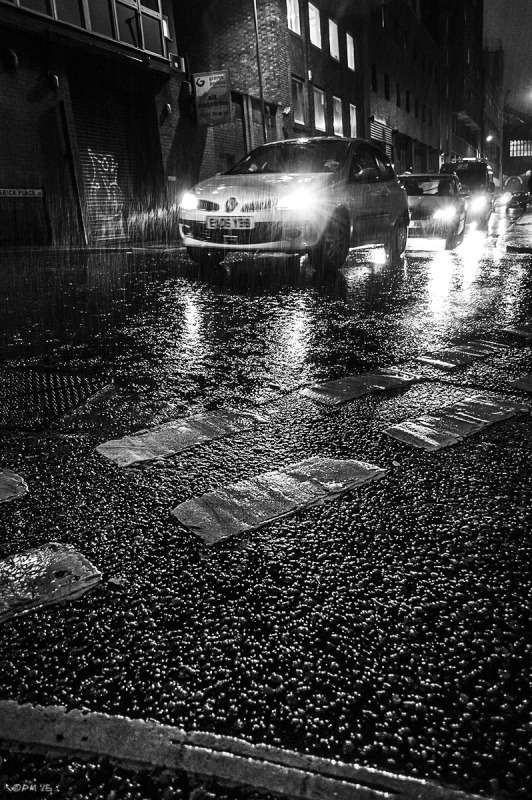 Cars in rain at night time on wet road with reflected head lights. Fredrick Place Brighton UK. Monochrome Landscape. © P. Maton 2015 eyeteeth.net