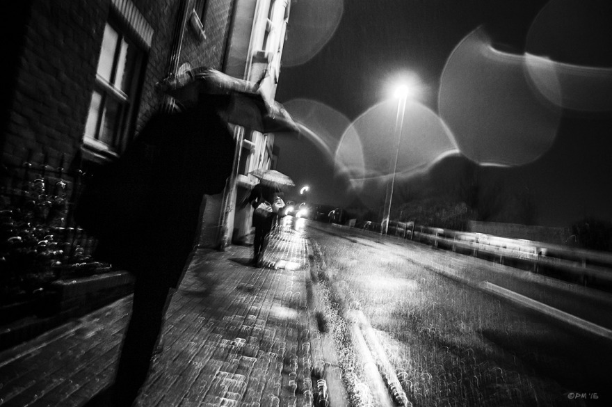 People with umbrellas waling in rain at night with droplets on lens, camera shake and street lamp reflected on road. Terminus Road Brighton UK. Monochrome Landscape. © P. Maton 2015 eyeteeth.net