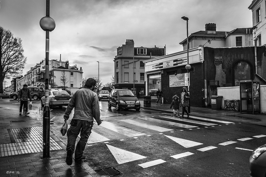 Man stepping onto zebra crossing in rain by Seven Dials roundabout. Chatham Place Brighton UK. Monochrome Landscape. © P. Maton 2015 eyeteeth.net