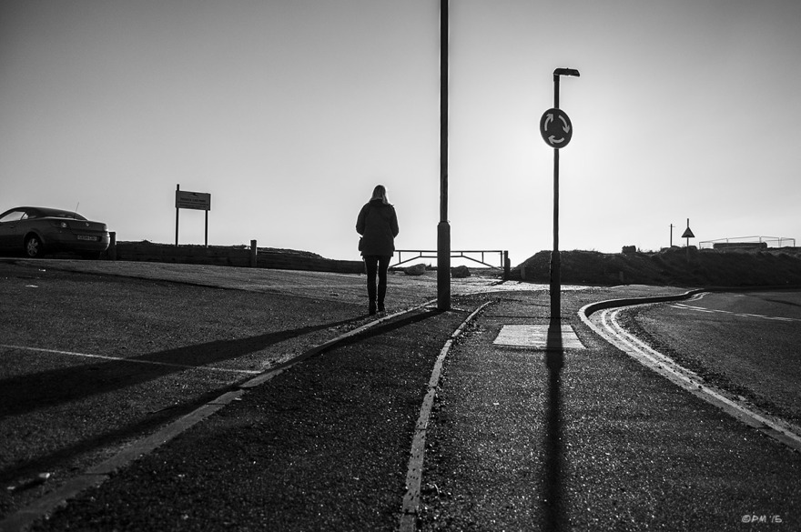 Silhouetted woman walking into sun at roadside next to lamp post and roundabout sign. Basin Road South Shoreham Harbour, Hove UK. Monochrome Landscape. © P. Maton 2015 eyeteeth.net