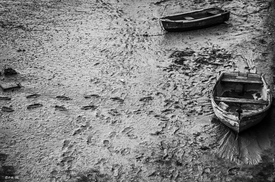 Old rowing boats sat on mud at low tide with footprints leading to them. River Adur Shoreham Harbour UK.  Monochrome Landscape. © P. Maton 2015 eyeteeth.net