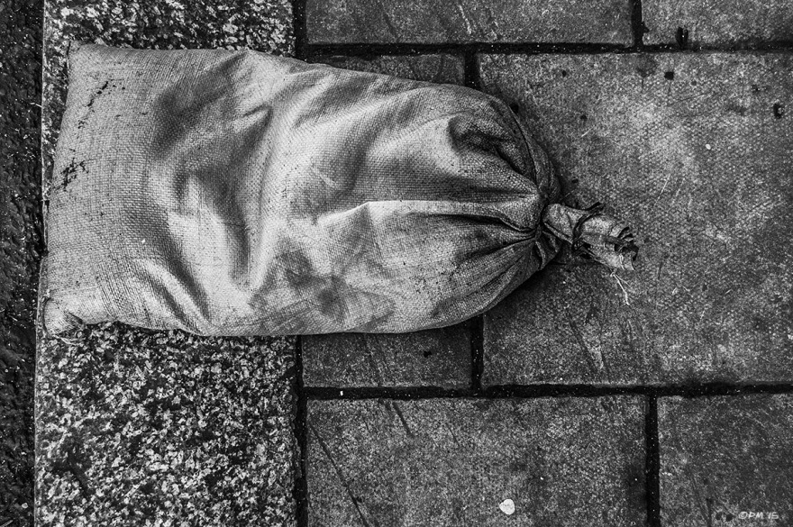 Sand / Ballast bag with tied end lying on paving slabs with granite curb stones. Old Steine, Brighton UK. Monochrome Landscape. © P. Maton 2015 eyeteeth.net