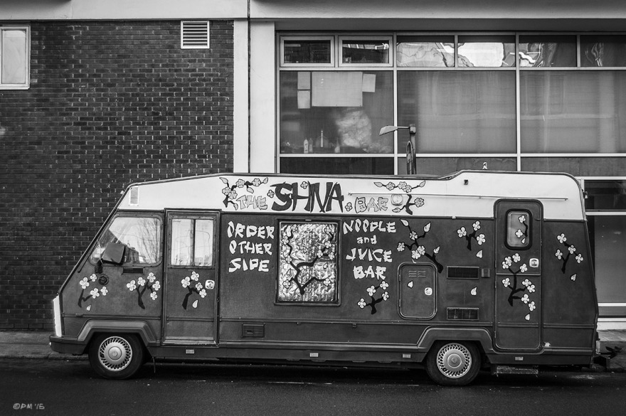 Converted camper van painted with flowers and sign saying The 'Shiva Bar' Nipple and Juice Bar parked on street.  Kingswood  Road Brighton UK. Monochrome Landscape. © P. Maton 2015 eyeteeth.net