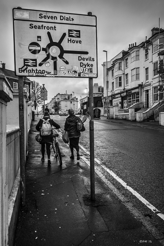 Two people walking in rain under road sign for Seven Dials roundabout. Chatham Place Brighton UK. Monochrome Portrait. © P. Maton 2015 eyeteeth.net