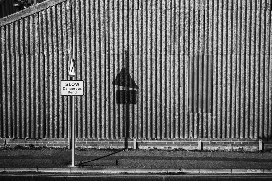 Road sign saying SLOW Dangerous Bend casting shadow on corrugated warehouse wall. abstract textures. Basin Road South Shoreham Harbour, Hove UK. Monochrome Landscape. © P. Maton 2015 eyeteeth.net