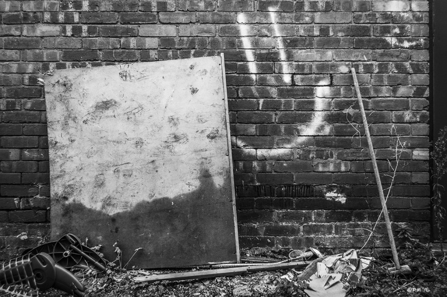 Smiley face sprayed on brick wall with detritus on floor. Marion Road Hove UK. Monochrome Landscape. © P. Maton 2015 eyeteeth.net
