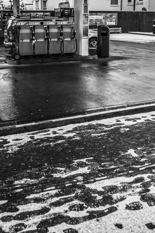 Petrol / Gas station pumps and forecourt  with footprints in snow on pavement / sidewalk. Dyke Road, Brighton UK. Monochrome portrait. © P. Maton 2015 eyeteeth.net