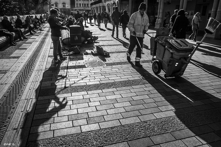 Buskers and street sweeper among people walking down paved street silhouetted by winter sun. New Road, Brighton UK. Monochrome Landscape. © P. Maton 2015 eyeteeth.net