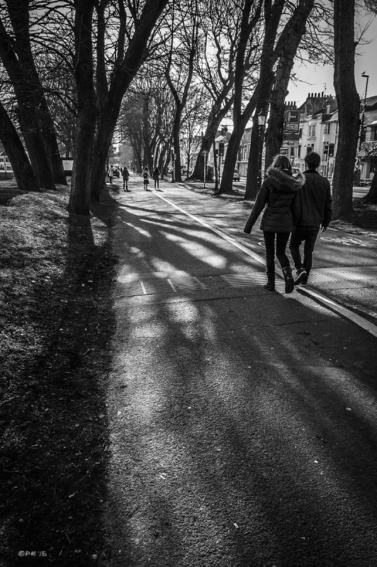 Young couple walking along white line on path leading through Elm Trees by The Level, Ditchling Road Brighton UK. Monochrome Portrait.  P. Maton 2015 eyeteeth.net