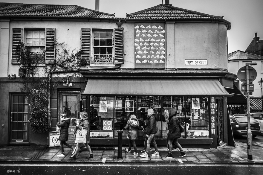Young people walking under awning  of Mama San cafe in rain with cloud poster and windows above. Tidy Street North Laine Brighton UK. Monochrome Landscape. © P. Maton 2015 eyeteeth.net