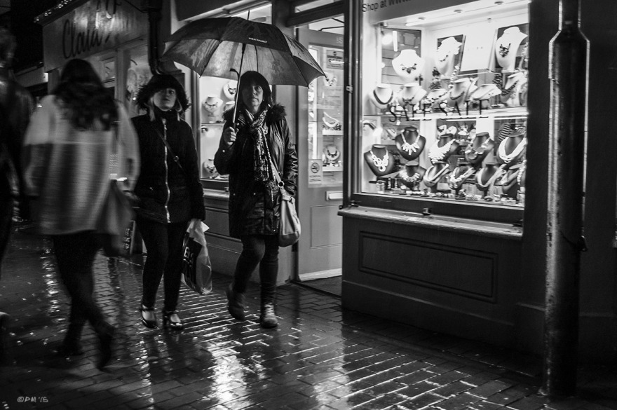 Mother and daughter with umbrella waling passed jewellers shop in rain at night. Kensington Gardens Brighton UK. Monochrome Landscape. © P. Maton 2015 eyeteeth.net