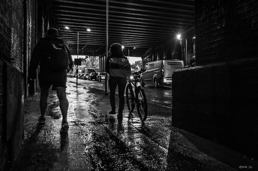 Silhouetted people walking on wet pavement under bridge with passing traffic. New Englad Road, Brighton UK. Monochrome Landscape. © P. Maton 2015 eyeteeth.net