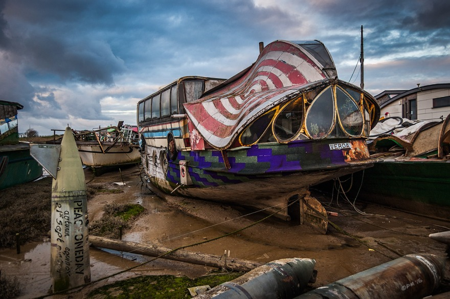 'Verda' houseboat with coach / bus and unusual teardrop windows under coulurful roof at stern sitting on mud flats at low tide with military tanks proclaiming 'Peace one day'.  River Adur Shoreham Harbour UK. Colour Landscape. © P. Maton 2015 eyeteeth.net