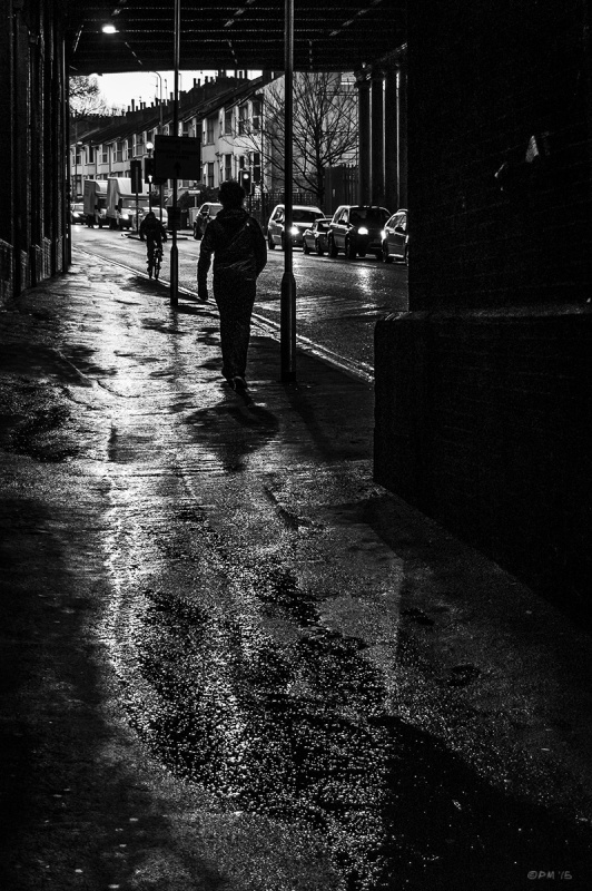 Silhouetted person walking on wet pavement under viaduct with passing traffic. New England Road, Brighton UK. Monochrome Landscape. © P. Maton 2015 eyeteeth.net