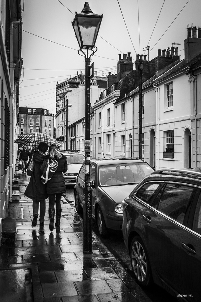 Two women walking under umbrella in rain passed lamp post and parked cars. Tidy Street North Laine Brighton UK. Monochrome Portrait. © P. Maton 2015 eyeteeth.net