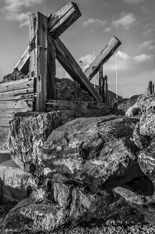 Wooden Sea defence on top of boulders with scattered clouds in sky. Shoreham Sussex UK. Monochrome Portrait. © P. Maton 2015 eyeteeth.net