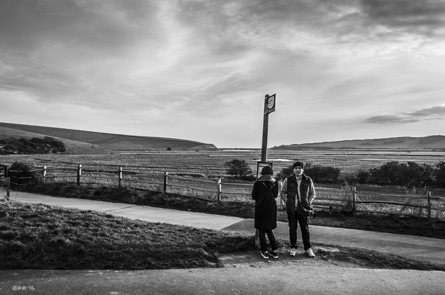 Oriental couple waiting at countryside bus stop with landscape view down Cuckmere Haven , Seven Sisters National Park, East Sussex UK. Monochrome Landscape. © P. Maton 2015 eyeteeth.net