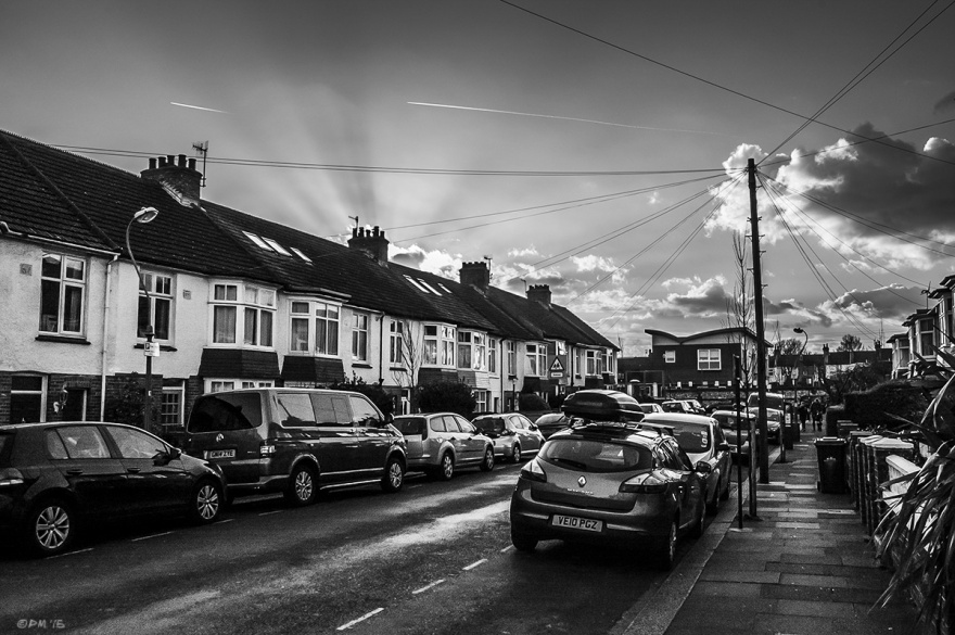 Sunrays radiating over roofs of terrace of houses with parked cars in street and clouds. Marion Road, Hove, East Sussex. Monochrome Landscape. © P. Maton 2015 eyeteeth.net