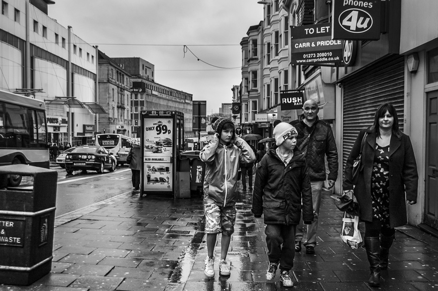 Family walking along shopping street in the rain, early evening. North Street, Brighton UK. Monochrome Landscape. © P. Maton 2015 eyeteeth.net
