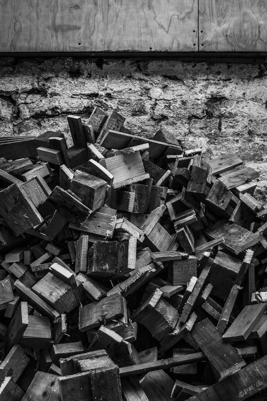 Pile of sawn up shipping palette wood with old painted brick wall and wooden shuttering behind. Abstract Monochrome Portrait. Coachwerks Brighton UK.  © P. Maton 2015 eyeteeth.net