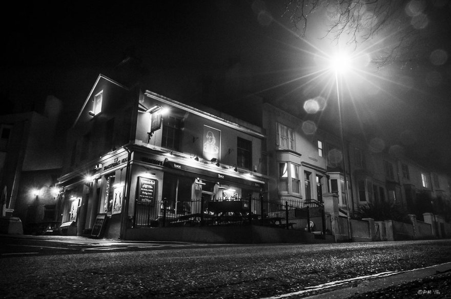 Night time view of pub on corner with road and street lamp light flare in mist. The Shakespeare's He'd pub, Brighton UK. Monochrome Landscape. © P. Maton 2015 eyeteeth.net