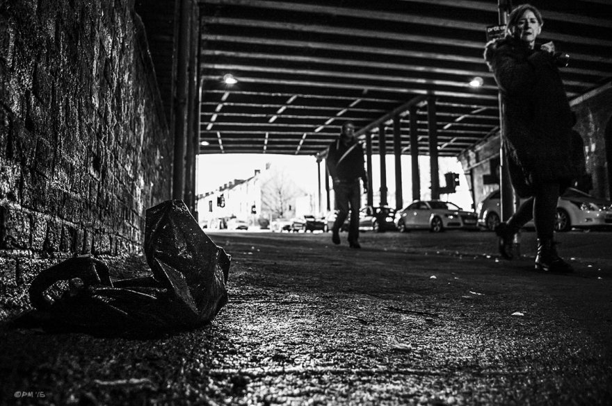 Black plastic bag on wet asphalt under viaduct with woman passing. New England Road, Brighton UK. Monochrome Landscape. © P. Maton 2015 eyeteeth.net